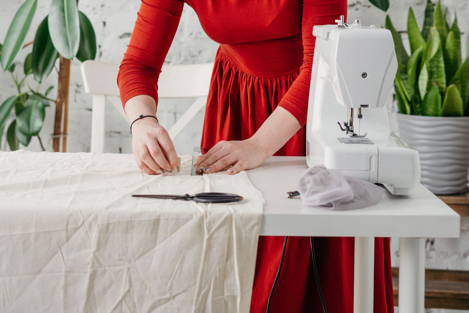 Woman is measuring textile to cut