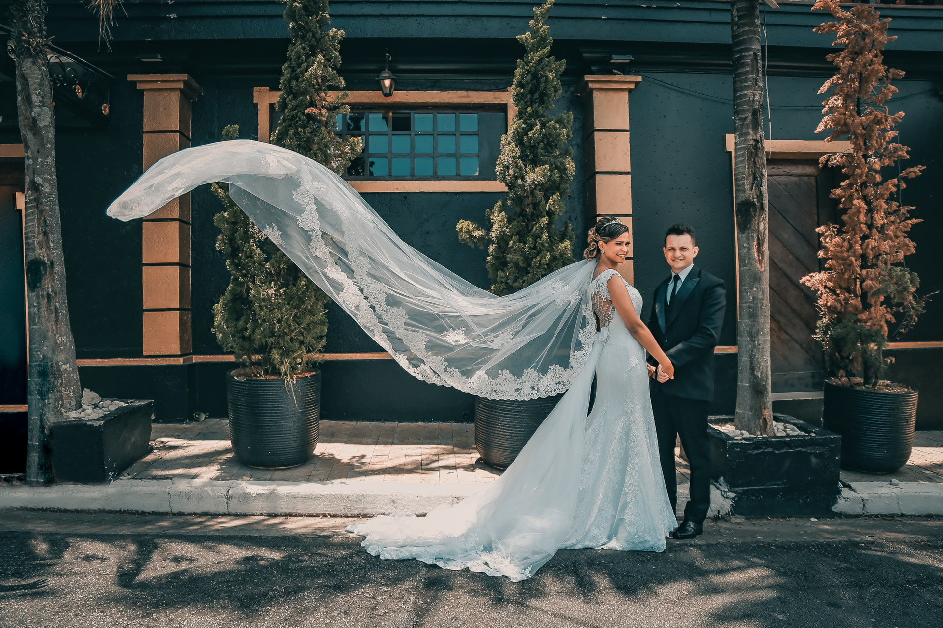 Wind is waving bride's veil while bride and groom are posing for wedding photography