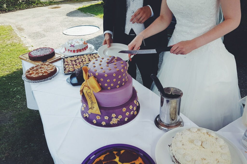 Couple Slicing Cake while posing for wedding photography