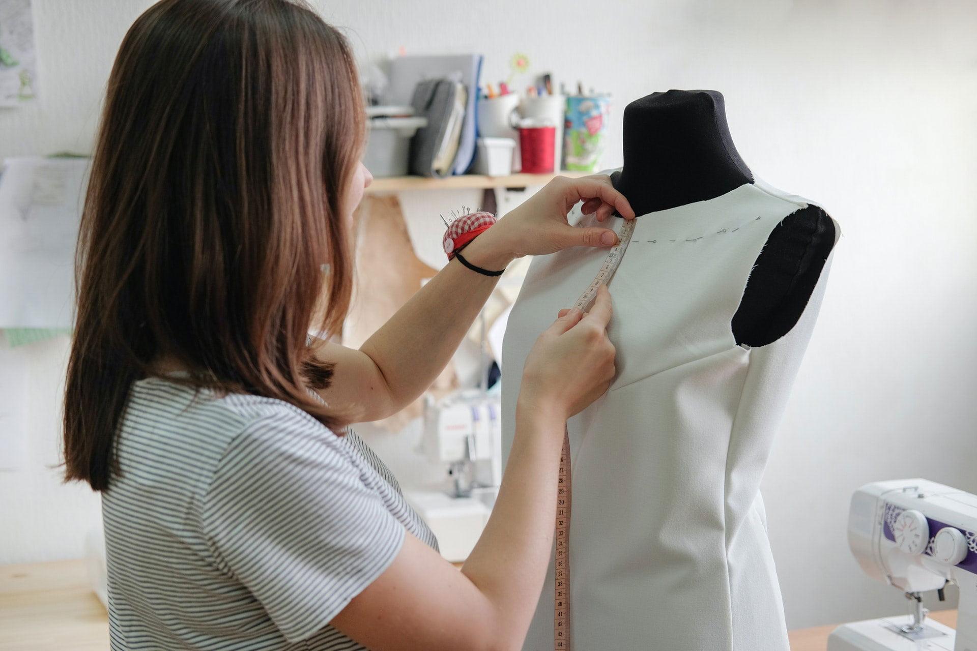 Female dressmaker measuring length on dress on mannequin