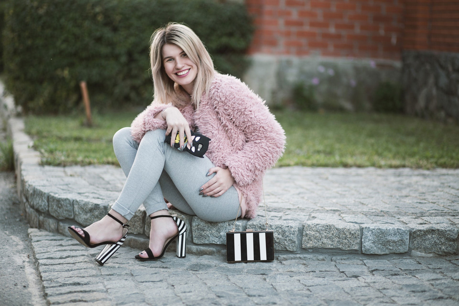 Stylish young woman sitting on pavement in city